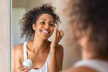 Black Girl Applying Lotion On Face