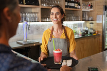 Smiling Waitress Serving Strawberry Smoothie