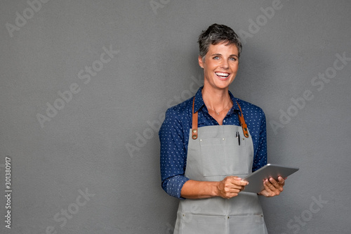Mature woman in apron holding digital tablet Fototapeta