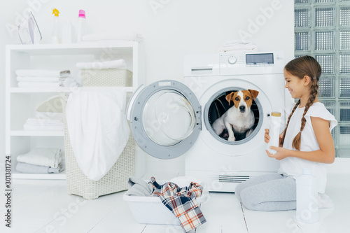 Fotografie, Obraz  Cheerful little girl stands on knees with washing detergent, poses near washing