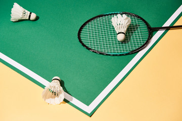 High angle view of badminton racket and shuttlecocks on green court on yellow surface