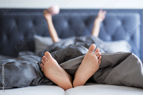 Obraz good morning concept - female hands and legs sticking out from the blanket - fototapety do salonu