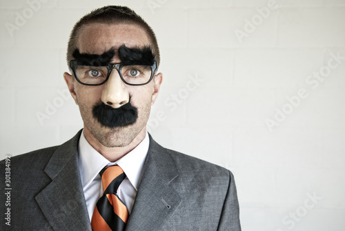 Fotografie, Obraz Businessman hiding his identity wearing a disguise of glasses with thick eyebrow