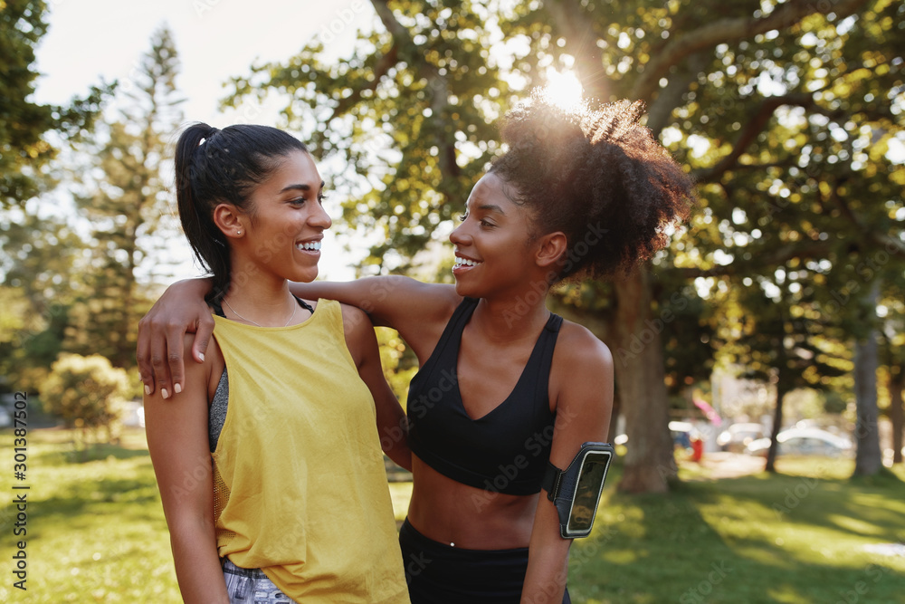 Fototapeta Portrait of a smiling multiethnic female friends hugging in a park on summers day - happy exercise friends smiling together in a park