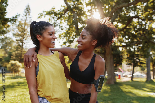 Fotografía  Portrait of a smiling multiethnic female friends hugging in a park on summers da
