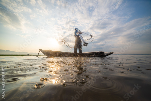 Picture of Asian fishermen on a wooden boat Thai fishermen catch fresh water fis Wallpaper Mural