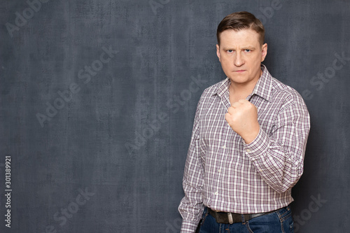 Portrait of angry irritated man raising hand with clenched fist Wallpaper Mural