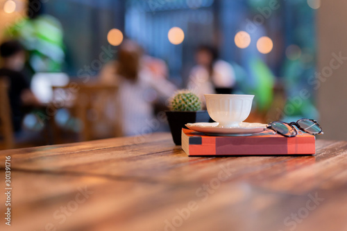 Coffee cup on top of reading book with eyes glasses on table in cafe Wallpaper Mural