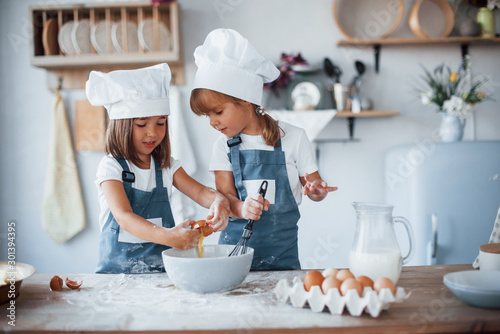 Photo Family kids in white chef uniform preparing food on the kitchen
