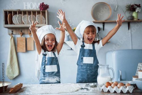 Fototapeta Having fun during the process. Family kids in white chef uniform preparing food on the kitchen obraz