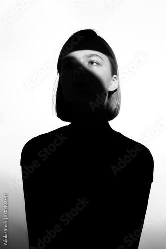 Fototapeta Fashionable beauty portrait. Black silhouette on white background. Girl with a spot of light on her face.  obraz na płótnie