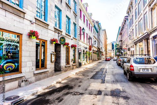 Montreal, Canada - May 28, 2017: Old town area with restaurant sign, and red geranium flower pot hanging by street during day outside in Quebec region city