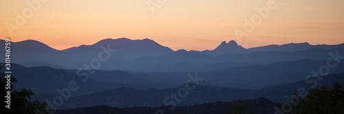 Fotografie, Obraz Panoramic silhouette of mountains against an orange sky.