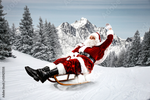 Foto auf Leinwand Rosa dunkel Red Santa Claus riding a wooden sled. An older man with a beard delivers presents to a child. Winter mountains landscape and snow-covered trees with frost. Fir branches, winter time. Christmas spells