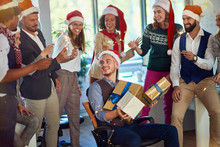 People Celebrating Winter Holidays Together At Work. Happy Business People In Santa Hat.