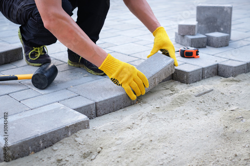 Foto The master in yellow gloves lays paving stones in layers
