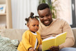 Leinwandbild Motiv family, fatherhood and people concept - happy african american father reading book for baby daughter at home
