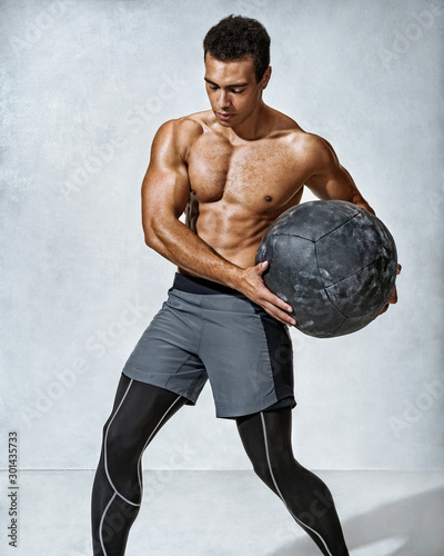 Fotomural  Muscular man doing twist exercise with med ball