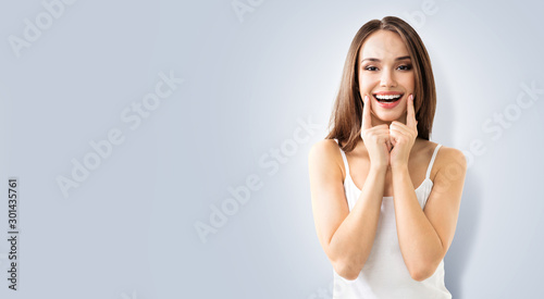 Happy woman pointing toothy smile Wallpaper Mural