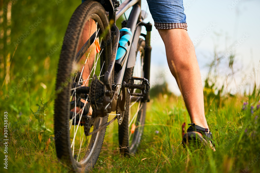 Fototapeta Legs of a male cyclist and mountain bike close-up