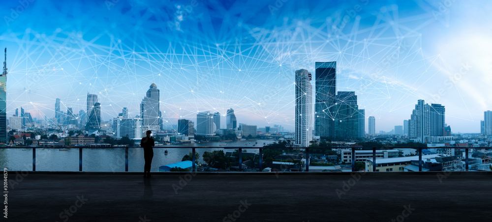 Fototapety, obrazy: Businessman standing using smart phone in modern space watching city night view.Business Wireless network and Connection technology concept.