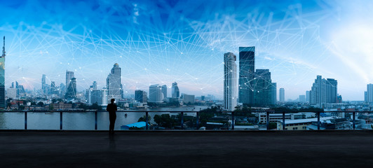 Businessman standing using smart phone in modern space watching city night view.Business Wireless network and Connection technology concept.