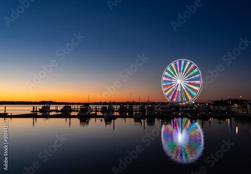 Obraz Illuminated ferris wheel at National Harbor near the nation capital of Washington DC at sunset - fototapety do salonu