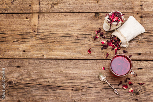 Recess Fitting Tea Hot hibiscus tea. Dry petals, linen sacks. Healthy food and self-care concept. Old wooden boards backgrounds