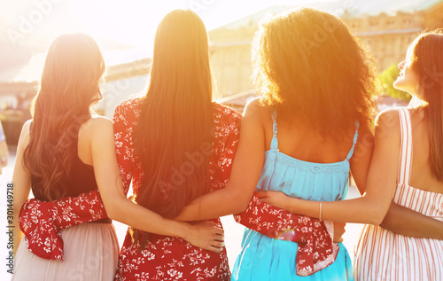 obraz dibond Calm women relaxation. Four beautiful girls are posing with their backs to the camera in multicolored dresses, hugging each other like best friends.