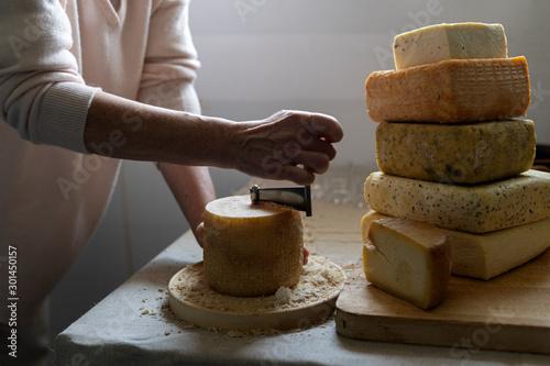 Pinturas sobre lienzo  Scraping Device of Swiss Cheese Tete de moine. A man cuts cheese.