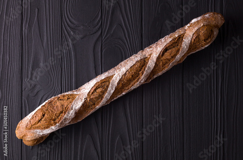Photo Top view photo of french rye baguette on black wooden table