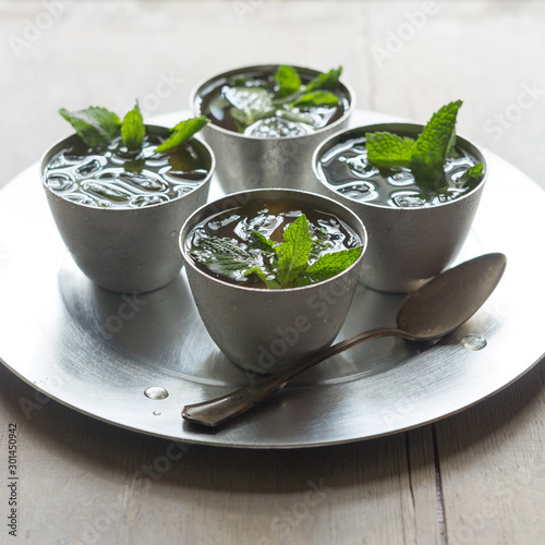 Valokuva  Top view of four mint julep cocktails with spoon on serving tray