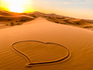 Moroccan desert heart landscape with sunset and dunes background.