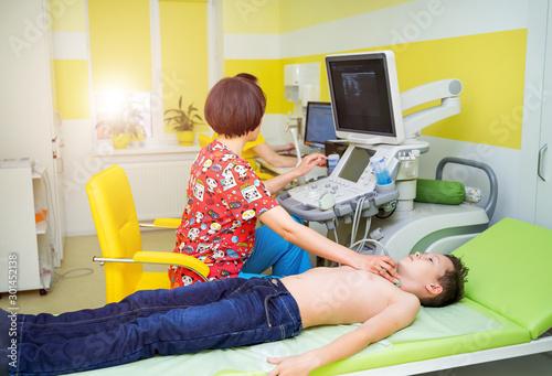 Obraz Doctor and a little boy patient. Ultrasound equipment. Diagnostics. Sonography. - fototapety do salonu