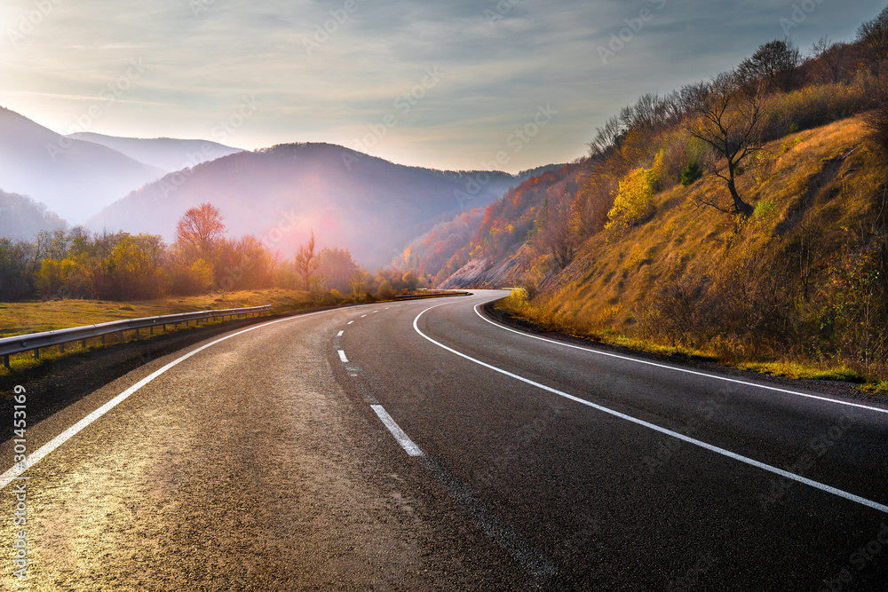 Fototapeta Highway in mountains in autumn evening