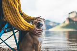 Fototapeta Zwierzęta - tourist friend girl together tender dog closed eyes on background mountain, female hands hugging puppy pet on lake shore nature trip, friendship love concept