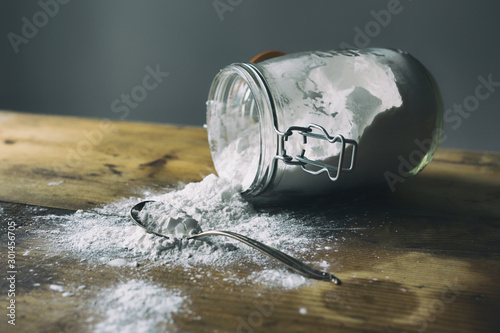 Glass jar filled with arrowroot powder spilled on a wooden table Wallpaper Mural