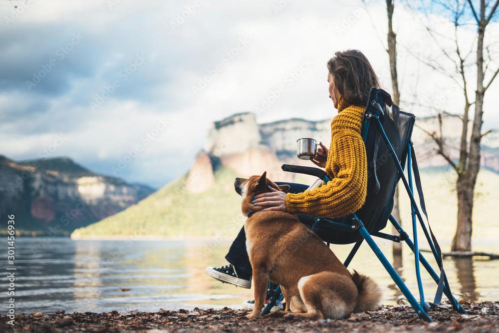 Fototapeta tourist traveler girl rest together dog on background mountain, woman drink tea hugging puppy pet on lake shore nature trip, friendship love concept
