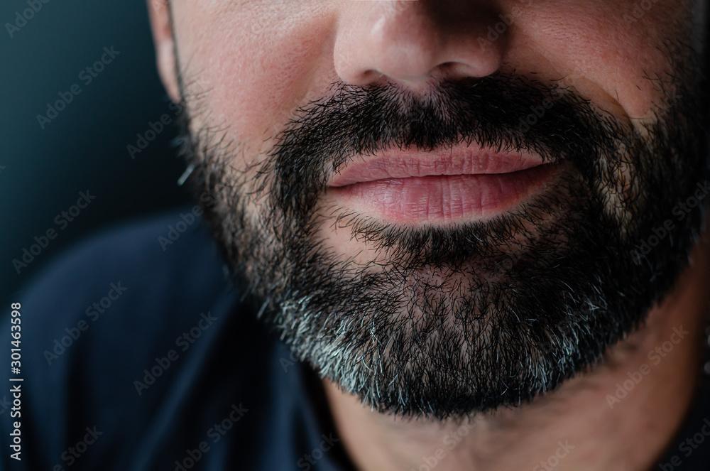 Fototapeta Cropped portrait of a smiling bearded brunette man. Close up