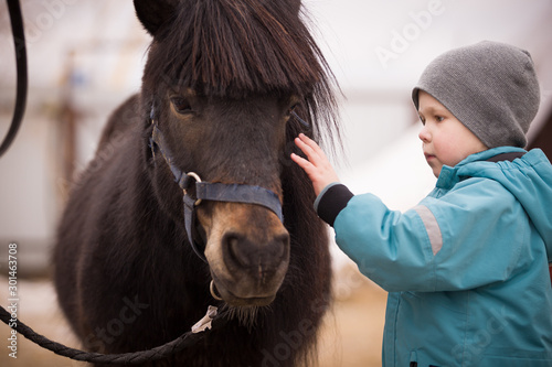 Obraz na plátně A little boy in turquoise overalls stroking an Icelandic pony horse with a funny forelock