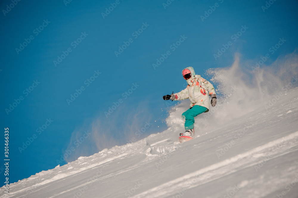 Fototapety, obrazy: Woman snowboarder riding down the hill in the background of clear sky