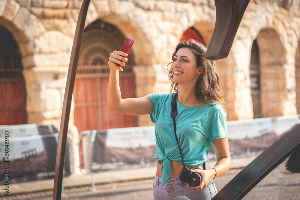 Fototapety, obrazy: Girl tourist on holiday in Verona taking a selfie, Italy, in front of the arena of Verona before the opera