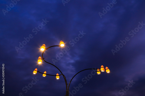Foto auf Leinwand Aubergine lila Beautiful vintage yellow lanterns glow against the blue sky in the clouds at night in the autumn or winter season. Mystical light in the evening