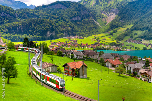Obraz Famous electric red tourist panoramic train in swiss village Lungern, canton of Obwalden, Switzerland - fototapety do salonu