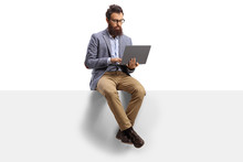 Bearded Guy With On A Laptop Sitting On A Panel