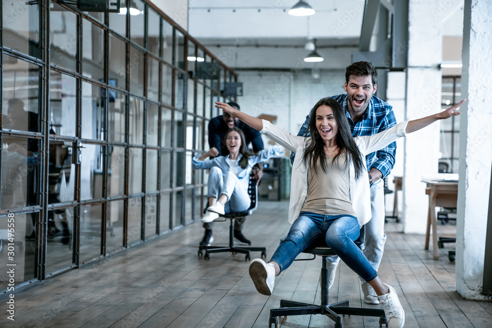 Fototapety, obrazy: Work hard play hard. Four young cheerful business people in smart casual wear having fun while racing on office chairs and smiling