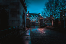 GLASGOW, SCOTLAND, DECEMBER 16, 2018: Spooky Cobbled Street Surrounded By Old European Style Buildings. Illuminated Only With Weak Light From Street Lamps.