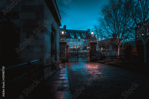 Fotomural GLASGOW, SCOTLAND, DECEMBER 16, 2018: Spooky cobbled street surrounded by old European style buildings