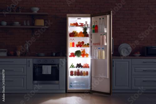 Fotografía  Open refrigerator in dark modern kitchen