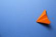 Orange paper plane on blue background